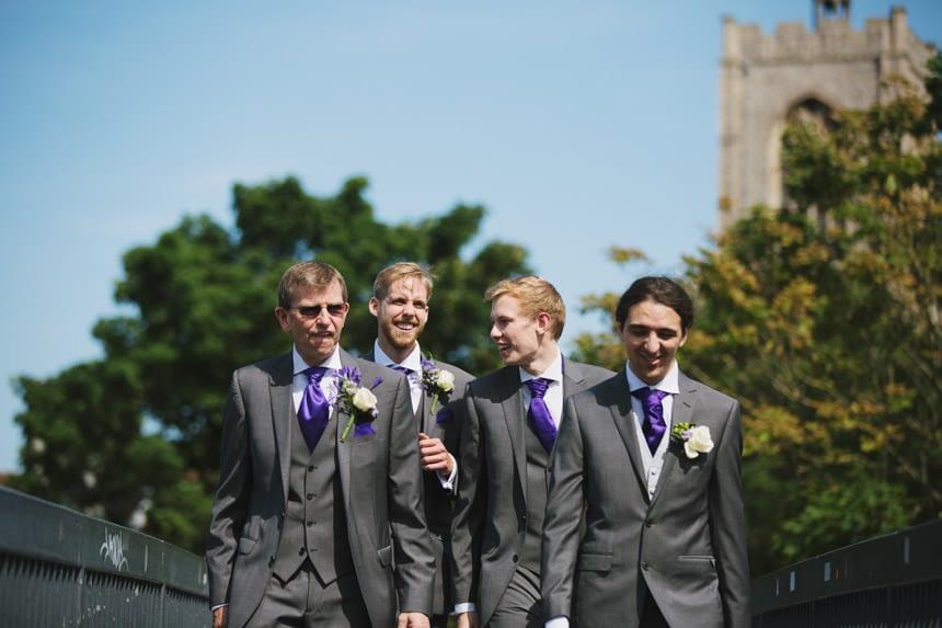 groom and groomsmen walk over bridge