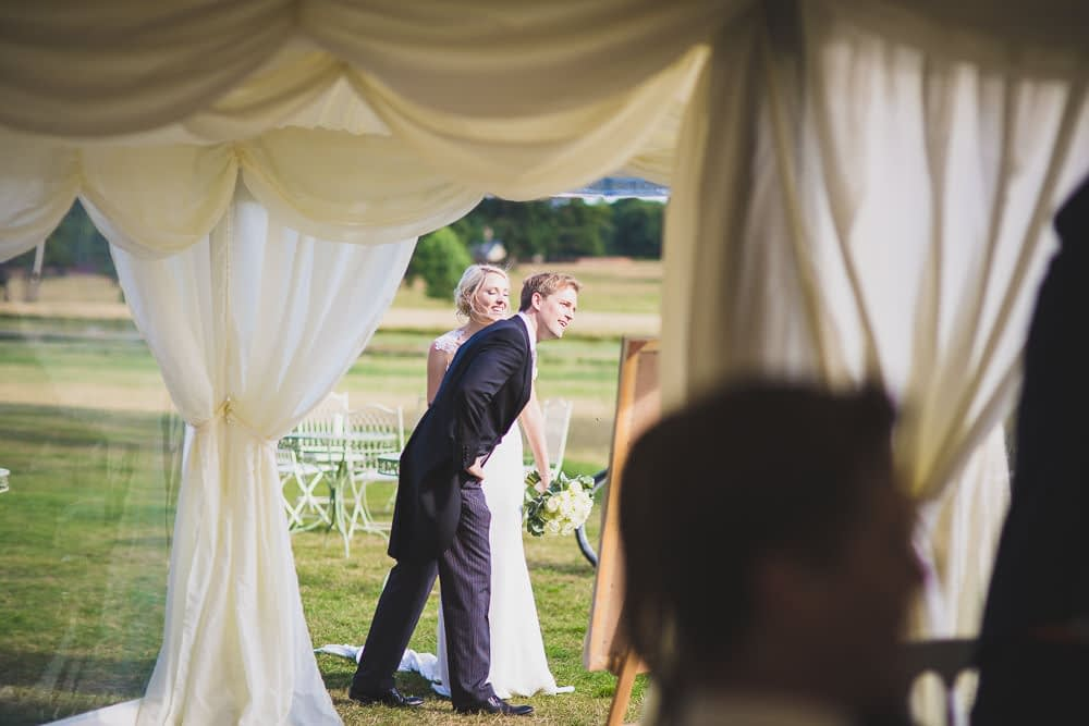 bride and groom waiting outside marquee