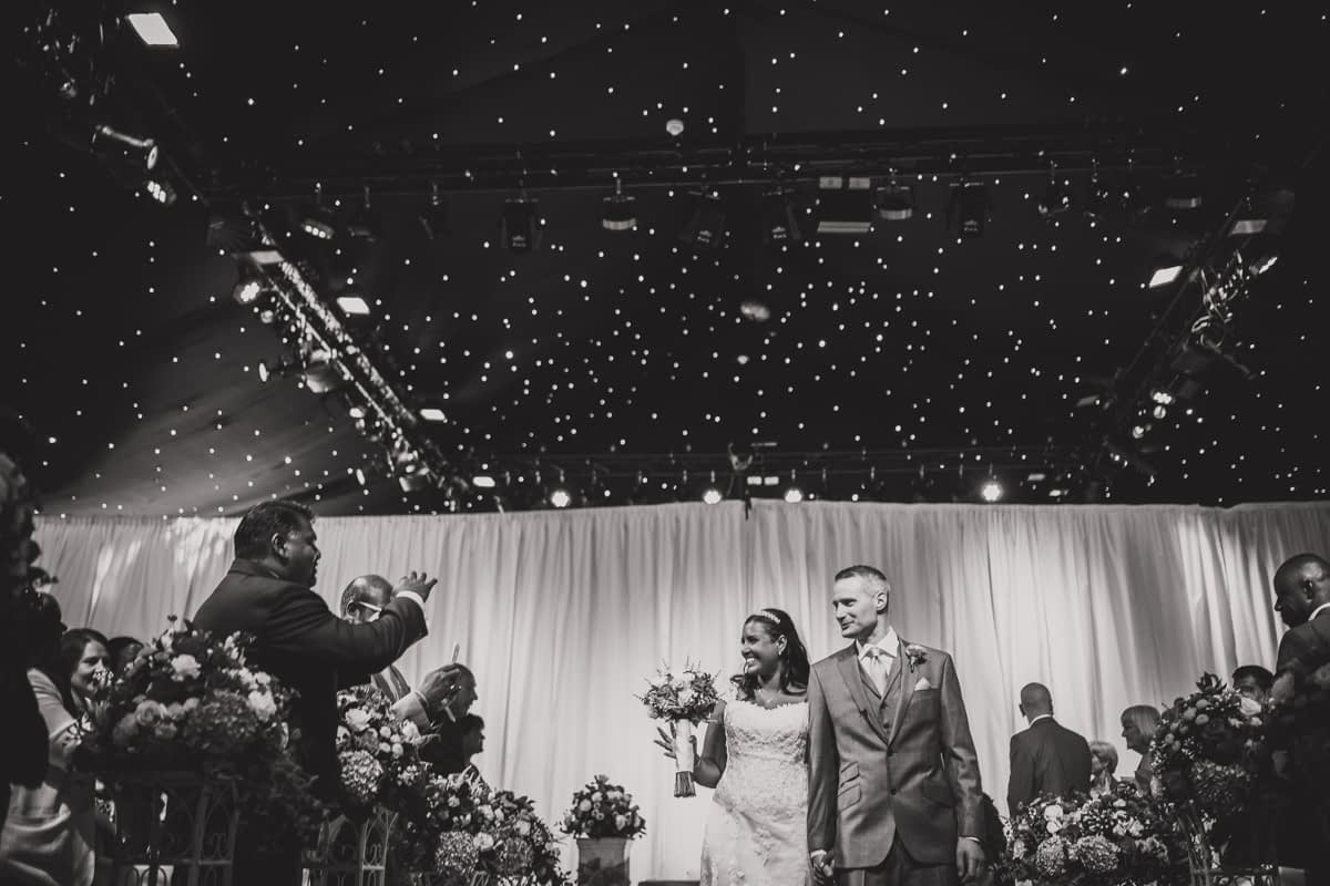 bride and groom waving to guests