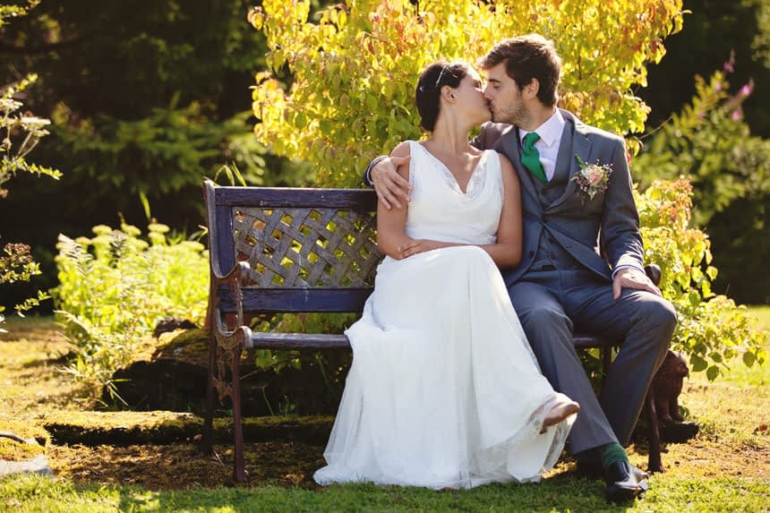 couple kissing on a bench