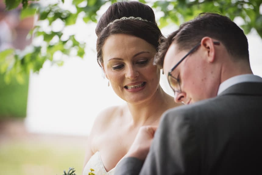 Bride and groom looking at Groom's button hole