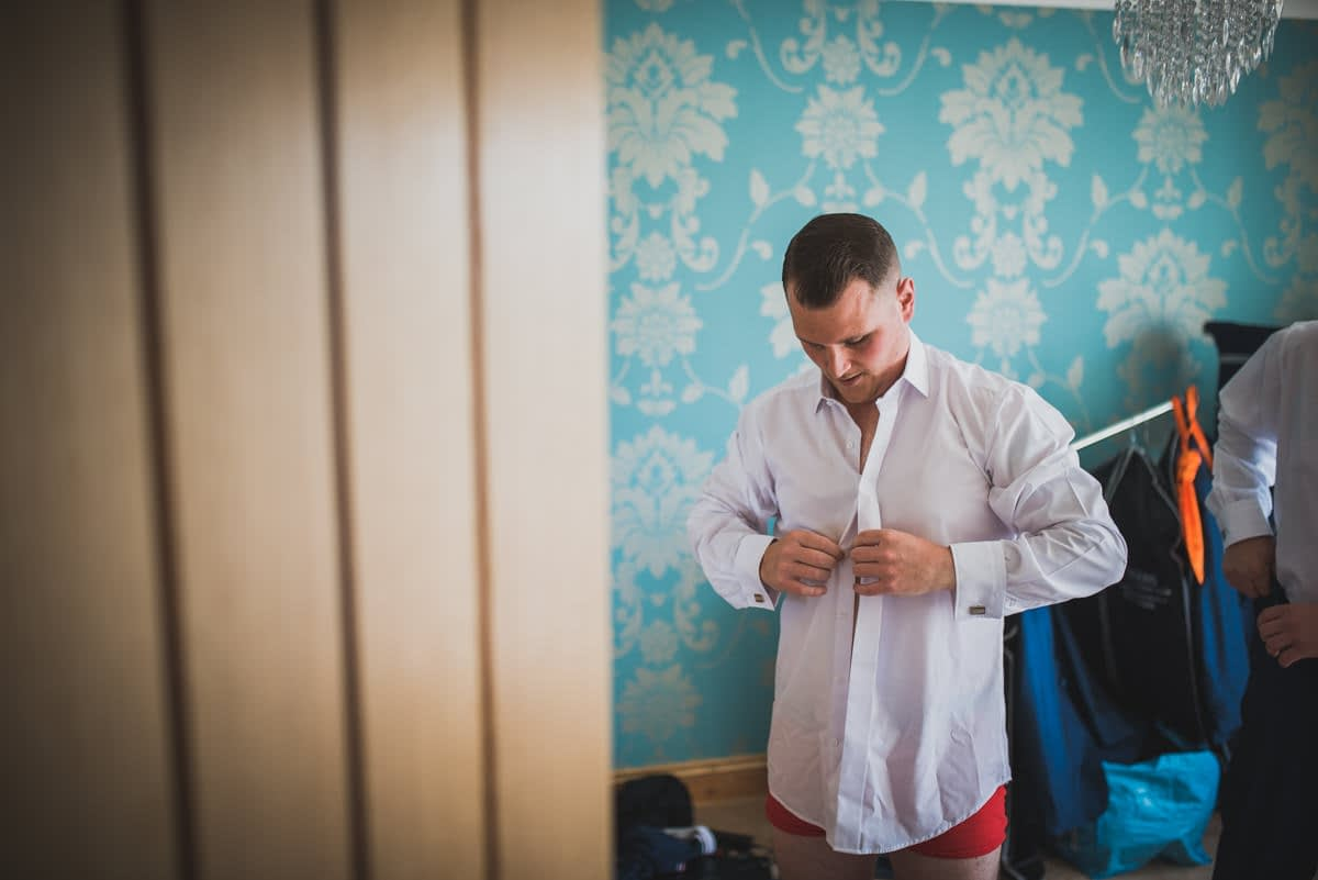groomsmen doing up shirt