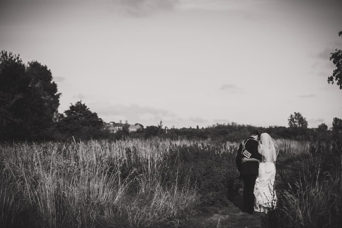 bride and groom walking in long grass