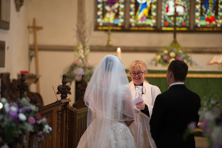 bride and groom shot from behind down aisle