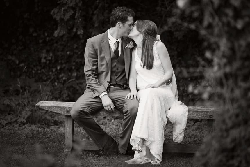 bride and groom kissing on bench black and white
