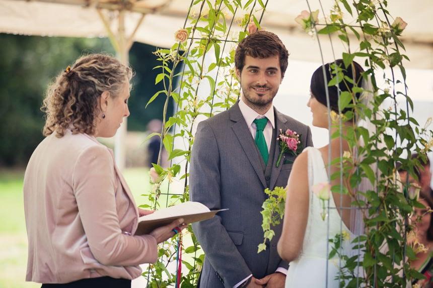 bride and groom under flower arch