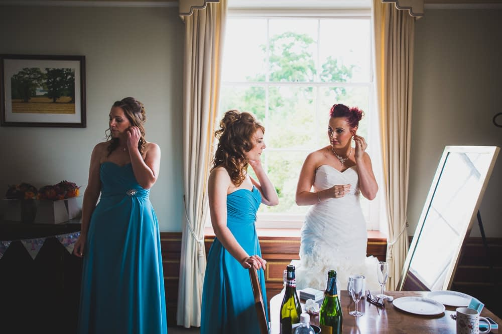 bridesmaids and bride putting ear rings on