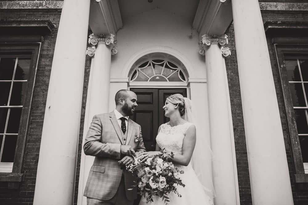 black and white photo of bride and groom on steps of Kimberly Hall