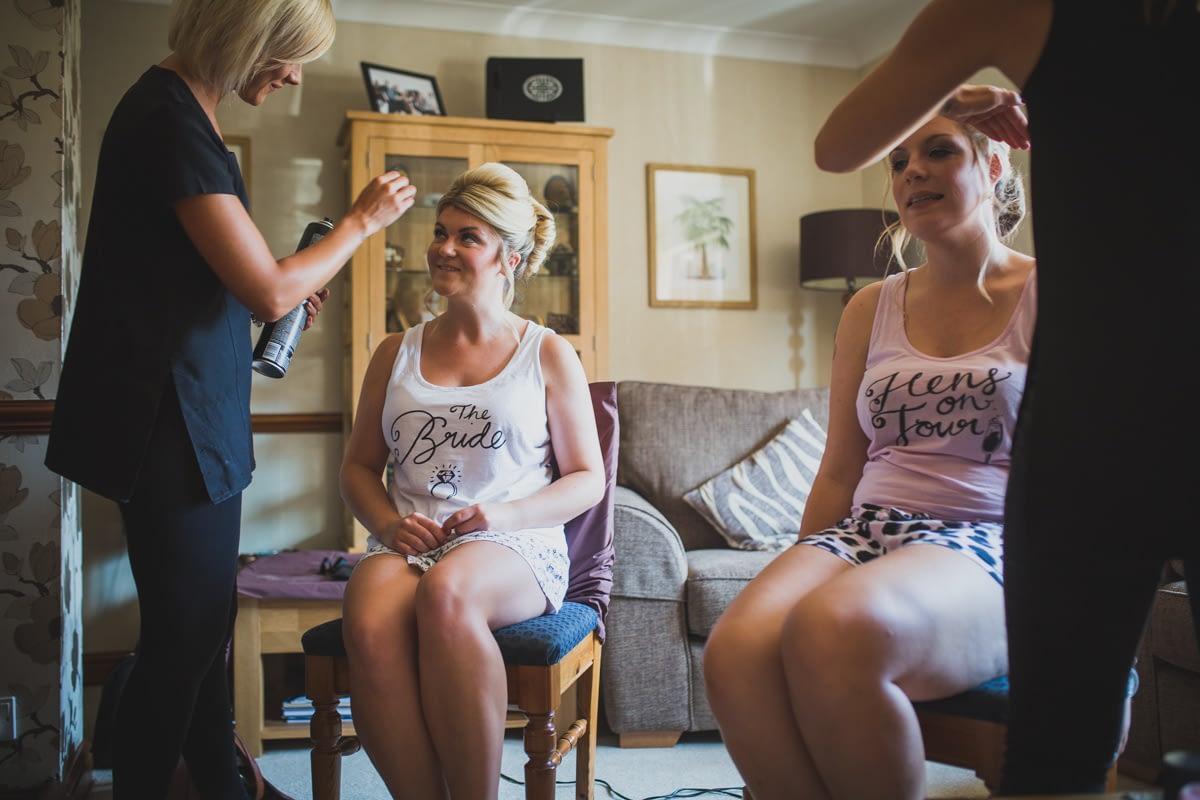 bride and bridesmaids having make up done