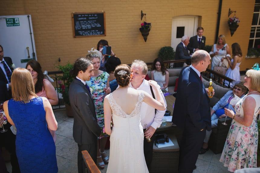 guest kisses bride on cheek