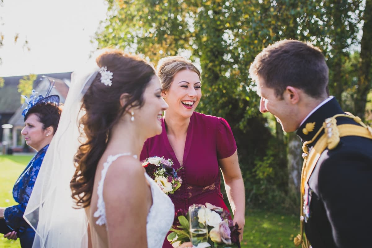 bridesmaid laughing with bride and groom