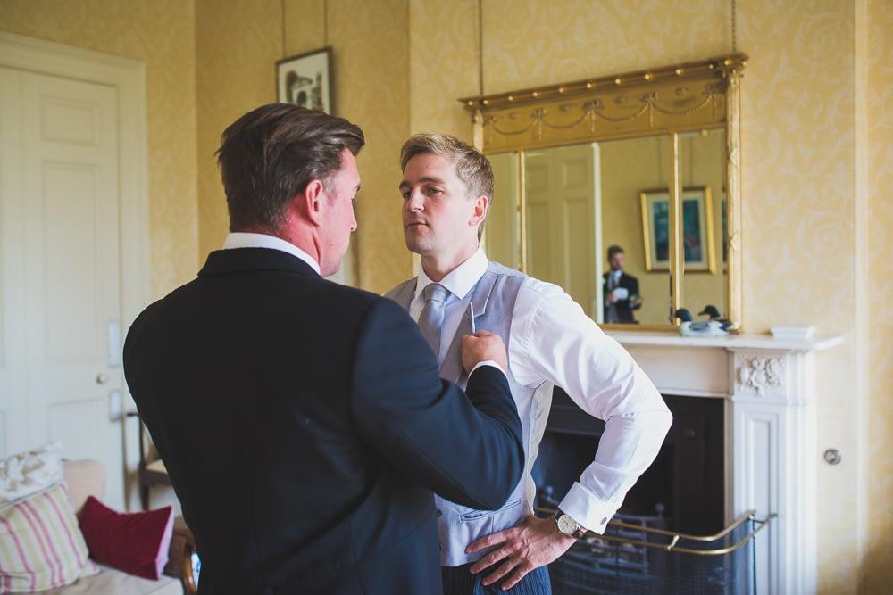 groom having tie adjusted
