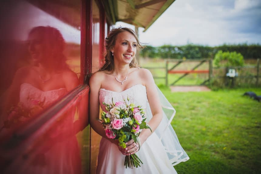 Bride leaning against a bus