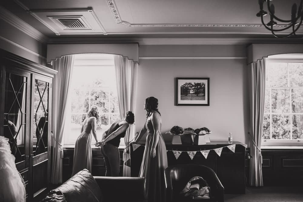 bride and bridemaids looking out window
