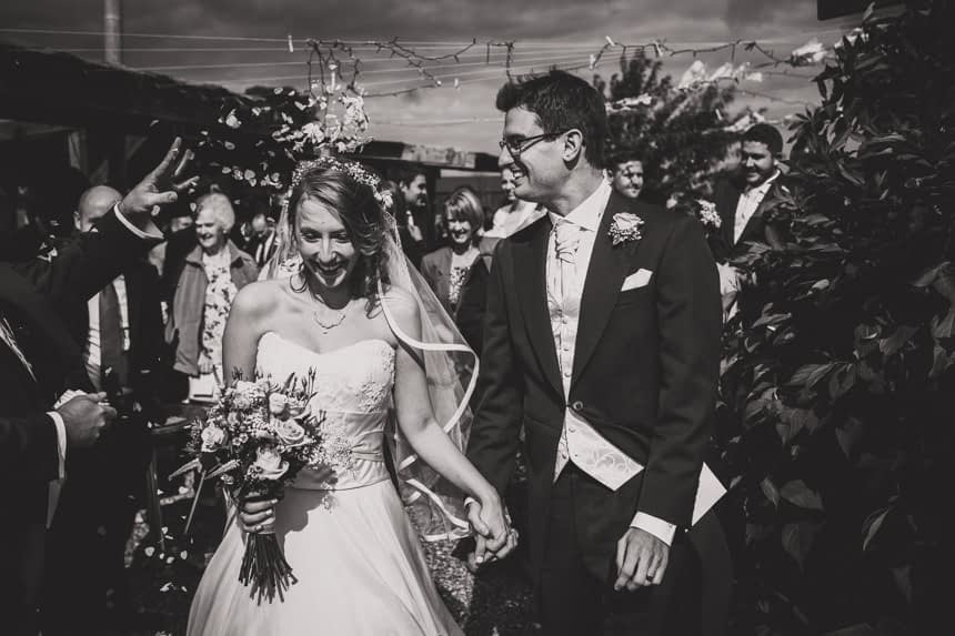 bride and groom walking in confetti