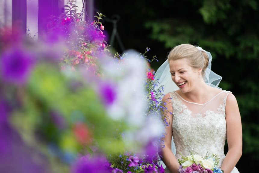 bride laughing next to wall flowers