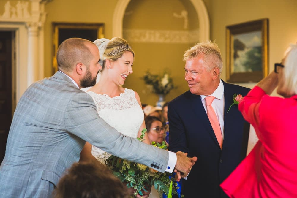 father of bride hands over daughter's hand to groom