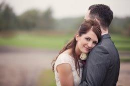 bride looks over grooms shoulder