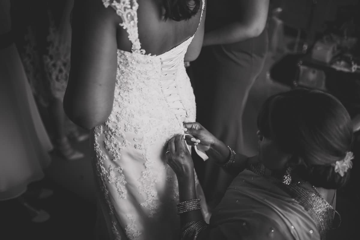 mother of bride helping bride into dress