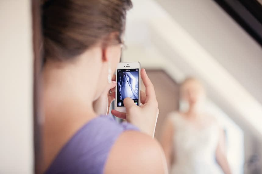 friend photographing bride with iPhone