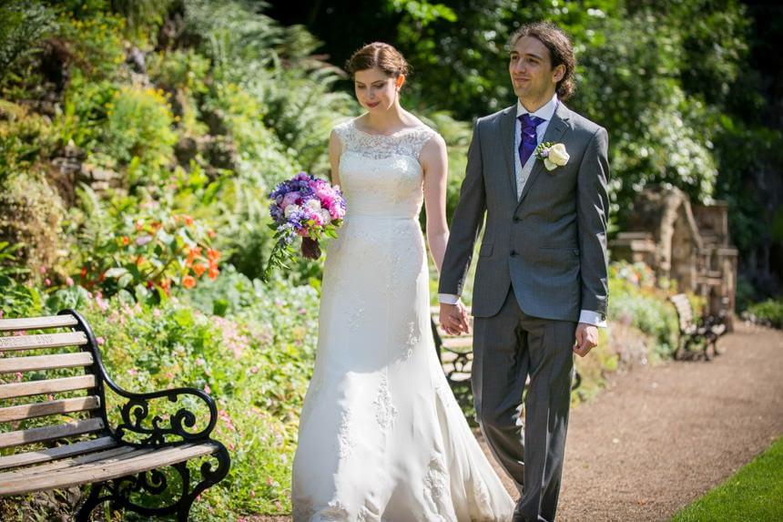 bride and groom holding hands walking