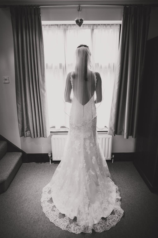 bride in dress standing in front of window