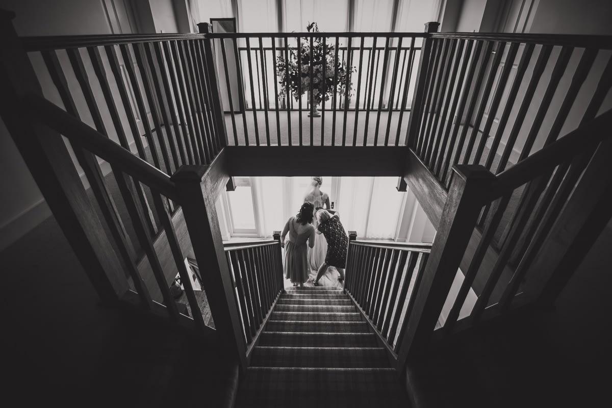 helping bride into dress