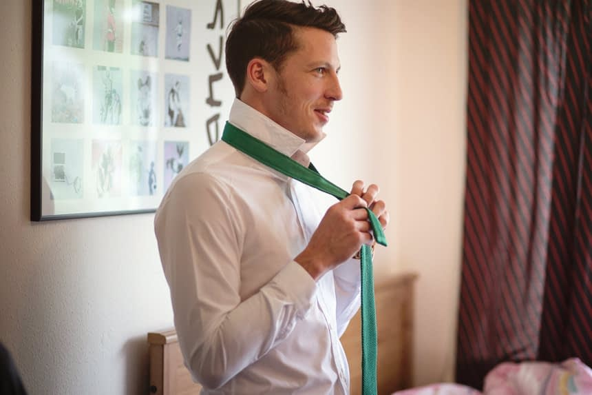 groomsmen tying tie