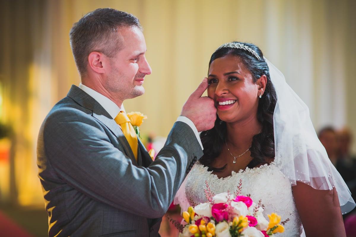 groom wiping tear from bride's eye
