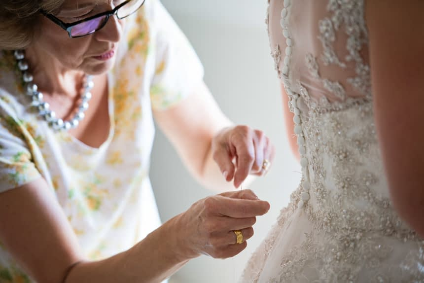 mother helping bride with buttons on back of dress