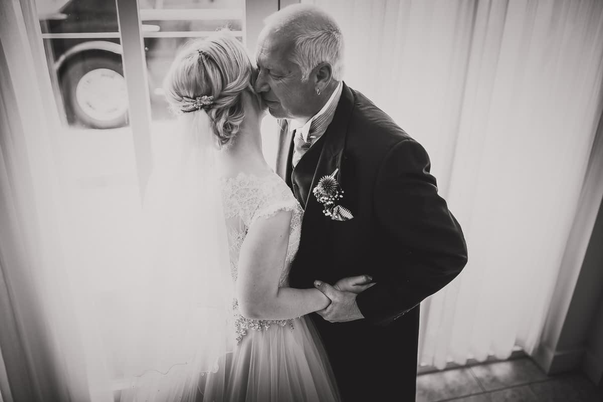 father of bride kissing daughter