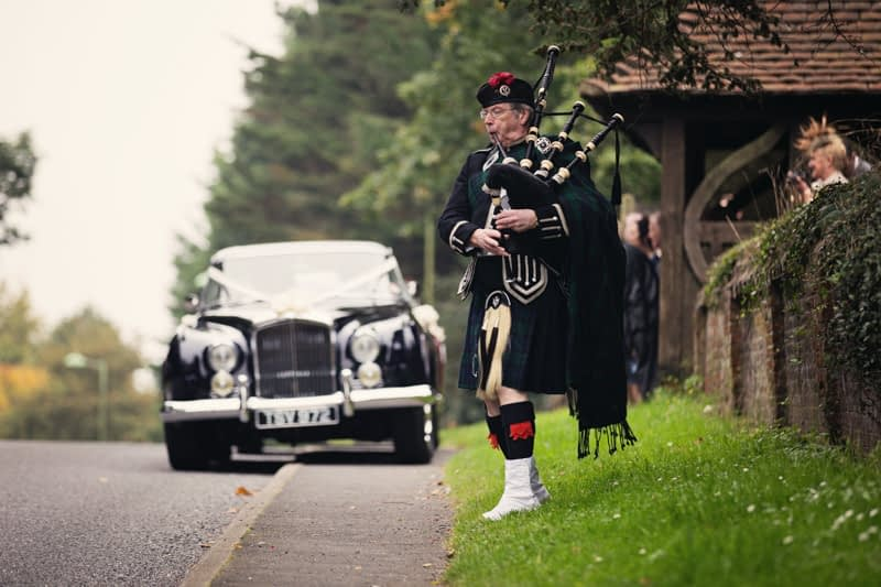 Piper plays as bride and groom leave in car