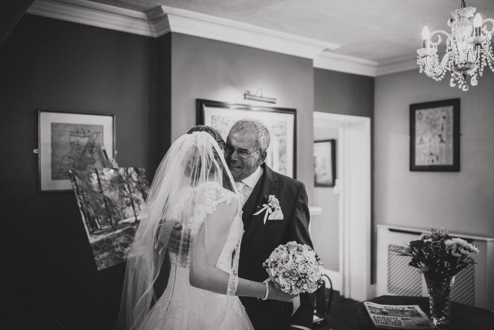 father of bride hugging bride