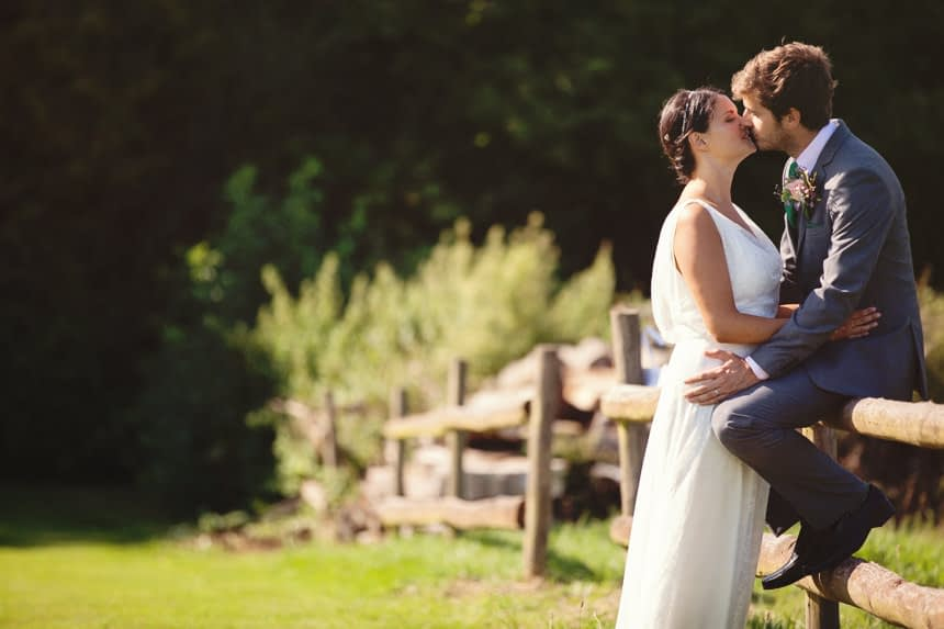 groom on a fence with bride kissing him