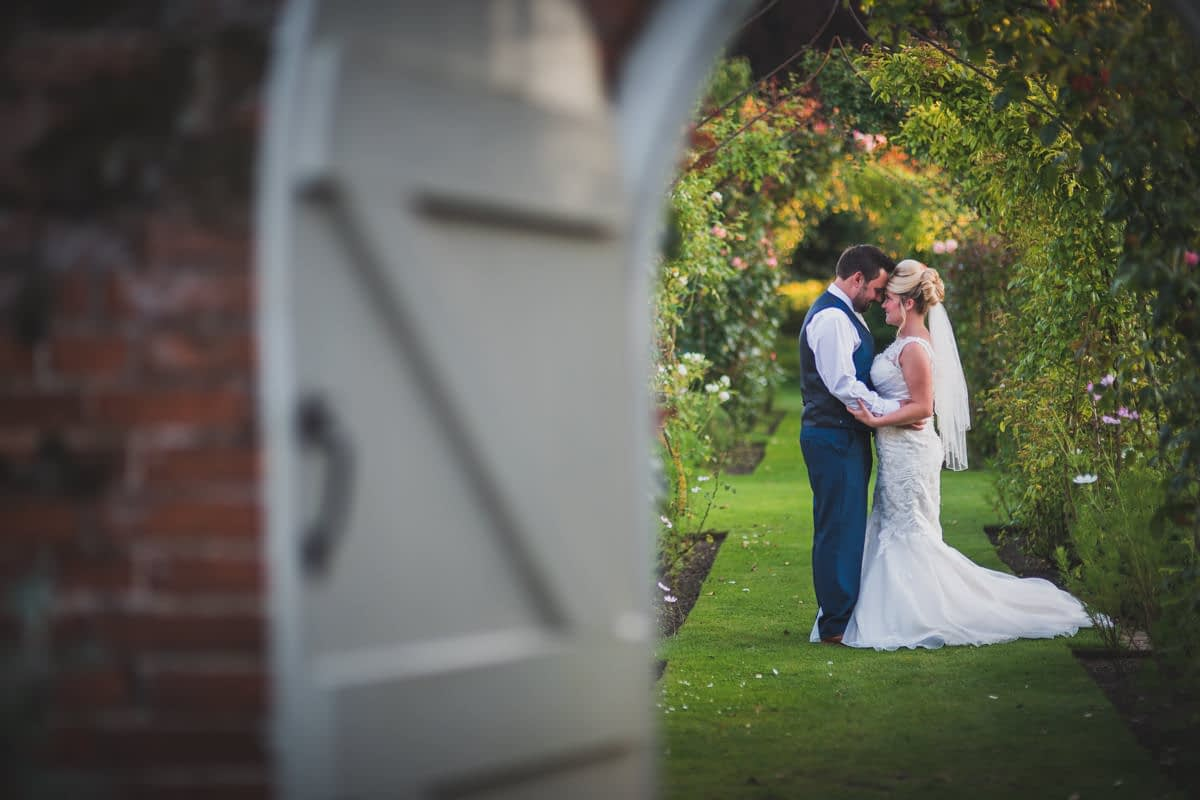bride and groom through archway
