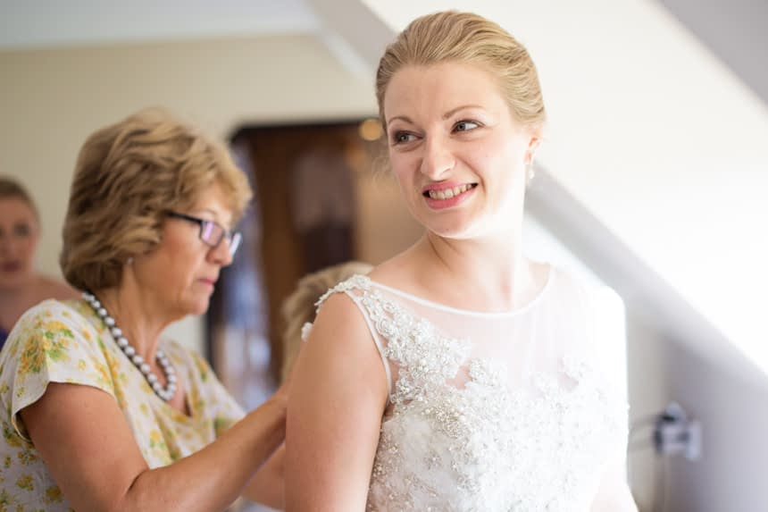 bride smiling with mother helping her into dress
