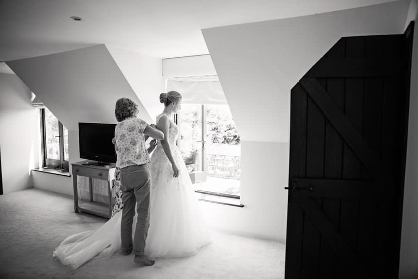 black and white, bride getting into dress
