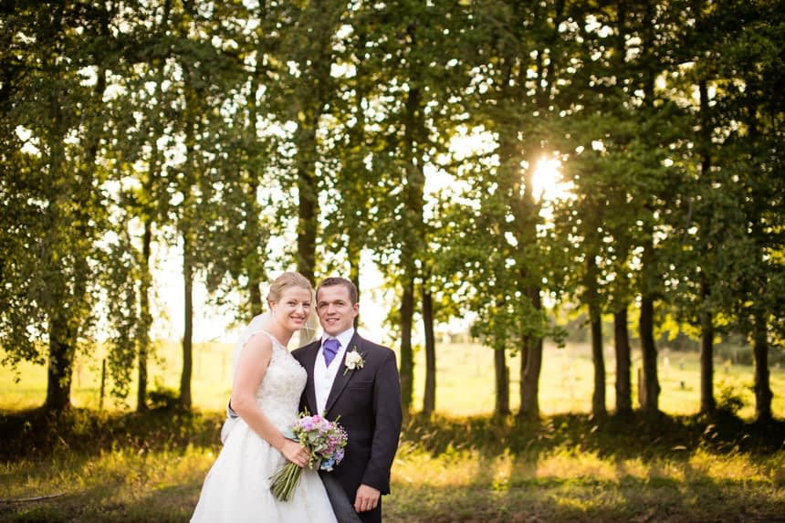 bride and groom close together in front of trees