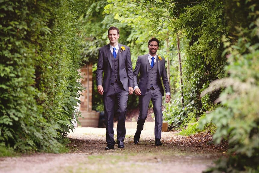 groom and usher walking to church