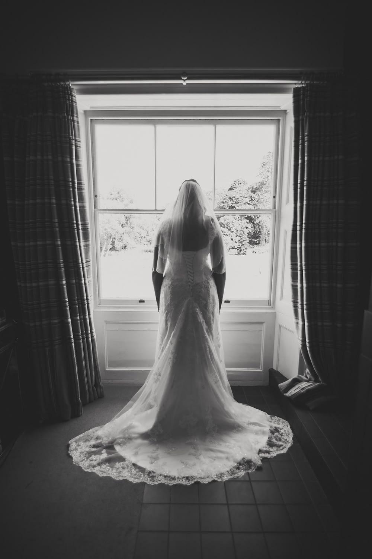 bride in dress in window